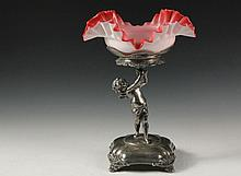 FIGURAL SILVER PLATE AND CASED GLASS COMPOTE - E.G. Webster & Son of Brooklyn, Standing Cupid supporting a ruffled pink and white glass bowl, circa 1885, 13