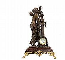 STATUE WITH COLUMN AND CLOCK - Circa 1890 French Bronze Finished Spelter Figure of a Fairy Enjoying Flowers, alongside a column containing a porcelain faced clock marked