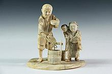 19TH C JAPANESE CARVING - Meiji Period Cabinet Figure or Okimono, of a market man parsing out two fish from his buckets for two young boys, one on the other's back, 5