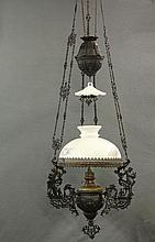 COUNTER-WEIGHTED PARLOR OIL LAMP - Fine example, circa 1880, in black painted cast iron, with milk glass shade and ruffled smoke bell, brass font and burner, the bracket having classical figures of sirens playing lyre...