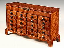 JEWELRY CABINET - 19th c. Tiger Maple Twenty Drawer Miniature Cabinet with overhanging hinged top concealing 36 compartments, the drawe