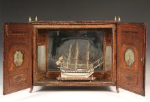 RARE NAPOLEONIC WARS CASED PRISONER-OF-WAR SHIP MODEL - Bone and Baleen Miniature Model of a British Man-o-War, circa 1805, housed in a straw marquetry decorated case, behind glass, with angled mirror backing so that ...
