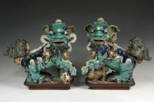 PAIR OF CHINESE ROOF TILE FINIALS - Ming Dynasty Glazed Stoneware Foo Dog Finials, in opposing stances, with green, blue and brown glazes, on later wooden stands, 15 1/2