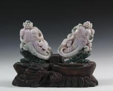 PAIR OF CHINESE JADEITE CARVINGS ON ONE STAND - Pale Lavender Gourds Nestled in Dark Green Leaves, resting in the original carved wooden stand decorated with fortune coins on tasseled cord