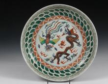 CHINESE PORCELAIN CHARGER - Large Shallow Charger decorated with Dragon and Phoenix struggling over flaming pearls amid clouds, ringed by bands of symbols for fire, waves and wind, having a blue geometric band on the ...