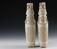 PAIR OF CHINESE IVORY COVERED URNS - Late 19th c. Ancestral Urns, one is signed, with reticulated covers having opposing writhing dragons emerging from the ocean, the tall, shouldered urns have foo dog lugs with loose...