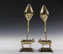 PAIR OF FIGURAL BRASS ANGLO-INDIAN CANDLESTICKS  - Featuring Standing Brahmin Bulls, with mechanical hinged lotus blossom petal cups that close fully, set on canted bracket pedestal, 15 1/2