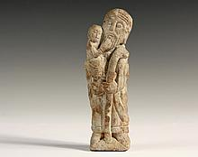 STONE SCULPTURE - Romanesque-Gothic Figure of Standing Saint Joseph Holding the Christ Child, late 11th to early 12th c, probably French, he is depicted with his staff in his left hand, the child is cradled in his rig...