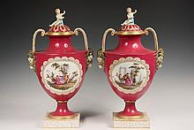 PAIR OF KPM URNS - Pair of Porcelain Urns in aubergine with gilt trim, 19th c underglaze blue marks, handpainted French bucolic scenes of courtship, ram's head mounted handles, figural putti knops seated on domed lids..