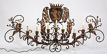 NINE-ARM WALL SCONCE - Wrought Iron and Gilt Pressed Steel Nine Arm French Style Wall Sconce with faux candles, shield having rampant lion and crown, acanthus leaf appliqués and dimensional cherry blossoms, wooden soc...