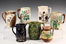 (7) MAJOLICA PITCHERS - 19th c. Pitchers in various forms, designs and glazes, mostly floral. 6 1/2