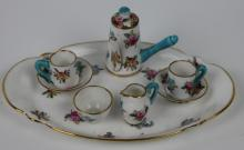 A Crown Staffordshire eight piece miniature coffee service, decorated in pattern A2912, with floral sprays, comprising an oval tray 12.5cm wide, a coffee pot and cover 4cm high, two cups and saucer a cream jug and a sugar bowl (8)