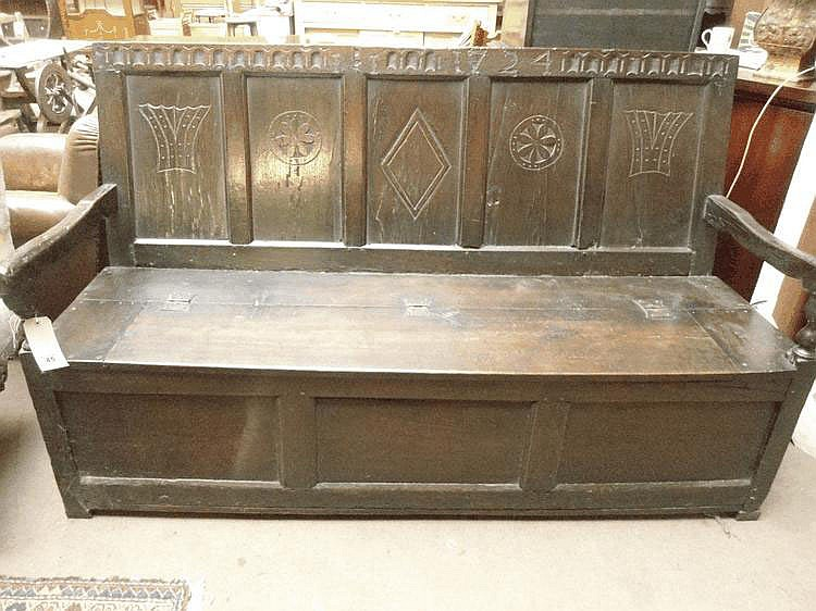 An early 18thC carved oak settle, carved with the