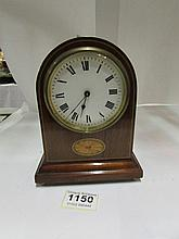 A small mahogany inlaid mantel clock