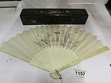 A Japanese ivory and silk fan, the guardsticks carved with flowers and figu