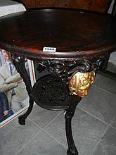 A cast iron pub table with stained wood top