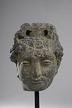 TETE de Boddhisattva au visage serein, les traits juvéniles empreints de beauté, la moustache frisée, les paupières mi-closes préconisant le regard à l'intérieur de soi, marqué au centre du front de l'urna symbolisant le troisième aeil, par une