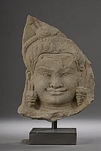 HAUT RELIEF de sanctuaire illustré d'une tête de devata souriante parée de lourds pendants d'oreilles.