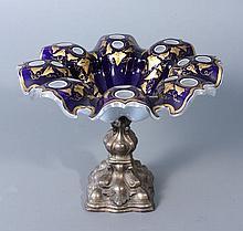 COUPE sur pied en métal ( ?) et bord dentelé en verre triplé d'émail blanc et d'émail bleu de Sèvres orné de feuillage doré et taillé de pontils. Haut.