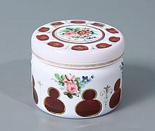 BOITE ronde en verre rose doublé d'émail blanc à décor de petits bouquets de fleur, et taillé à pontils. Haut.