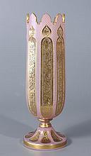 VASE DROIT à piédouche et bord dentelé en verre à décor de feuillages dorés stylisés, doublé d'émail rose taillé de motifs orientaux à semi de points dorés. Haut