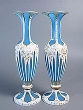 Paire de VASES BALUSTRES en opaline bleue doublée d'émail blanc taillé jeux d'orgues et réserves ogivales ; décor de feuillages doré (usures). Haut.