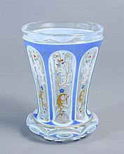 GOBELET à base excroissante en verre à décor de fleurettes colorées et de rinceaux blancs et dorés, doublé d'émail bleu de lin taillé de réserves en arcade. Base taillée à motifs de navettes. Haut.
