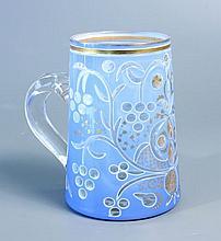 CHOPE en verre doublé d'émail bleu de lin gravé à motifs de grappes et de feuillage stylisés réhaussés de feuillages dorés ; anse incolore. Haut.