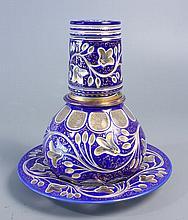 VERRE D'EAU à l'anglaise comprenant une carafe, son verre couvrant et son présentoir en verre doublé d'émail bleu taillé de guirlandes végétales stylisées ; décor de résilles et de rehauts et de filets dorés. Haut. totale