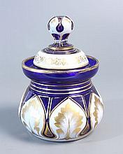 SUCRIER en verre bleu doublé d'émail blanc taillé en bandeau à rinceaux dorés et en feuilles stylisées à contours et nervures dorées. Haut.