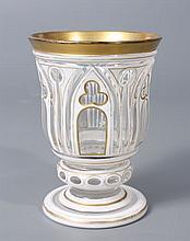 GOBELET à piédouche en verre doublé d'émail blanc taillé de motifs gothiques à filets dorés. Haut.