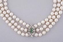 COLLIER à 3 rangs de perles de culture, le fermoir en or gris serti de brillants et d'émeraudes.  Expert Mme Hélène FOUTERMAN.
