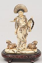 JAPON (XX°). GROUPE en ivoire sculpté représentant une jeune femme au chapeau, à ses pieds deux bouquetins. H 15cm (accident et recollage à la canne)