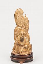 CHINE (XX°). SUJET en ivoire patiné sculpté représentant un sage en méditation devant rocher. Socle en bois vernis H 14cm
