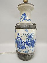 CHINE (XIX°). VASE en céramique craquelé de forme balustre à décor blanc bleu d'une scène de la vie domestique. Monté à l'électricité H 44cm