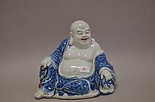 CHINE (XX°). BOUDDHA en porcelaine bleue et blanc, signature : Wei Houdai Zou. 15x17x10cm