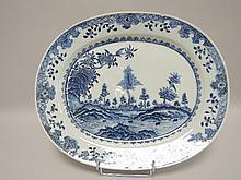 CHINE (XVIII°). PLAT creux ovale en porcelaine de la compagnie des Indes à décor bleu et blanc de paysages et d'oiseaux branchés 33,5x28cm (égrenures)