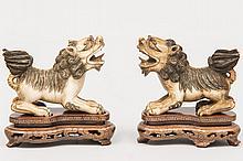 CHINE (XX°). Deux SUJETS en ivoire sculpté représentant des lions boudhiques. Socles en bois vernis 7x8cm