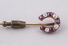 EPINGLE à cravate en or jaune ornée d'un motif fer à cheval sertie de 4 brillants et 5 rubis pb 6g