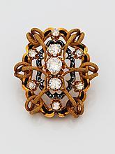 BROCHE en or jaune 18K 750 millièmes, polylobée, à décor d'entrelacs, partiellement émaillée noir et blanc, sertie de diamants de taille ancienne, l'un d'entre eux de forme poire au centre.
