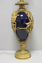 VASE monté en lampe de forme ovoïde en porcelaine émaillée de couleur bleu de Sèvres, la panse ornée de rinceaux croisés, les prises à tête de femme et reposant sur un piédouche godronné à rehauts d'or.