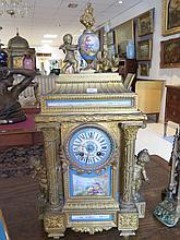 HORLOGE en alliage doré et porcelaine de Sèvres surmontée de puttis et d'amours.