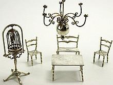 Een miniatuur zilveren vogelkooi in standaard, een tafel met 2 stoelen en een bankje en een bolkroonluchter