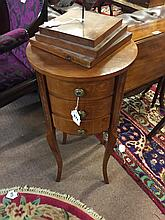 Mahogany circular bed side cabinet with three drawers.