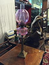 Oil lamp with brass column ruby glass bowl and football shade.