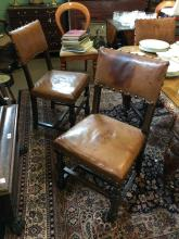 Set of six oak dining room chairs with leather upholstery.