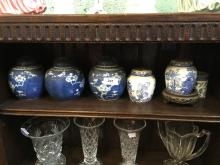Five blue and white ginger jars and a beaker.