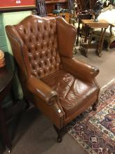 Leather upholstered wing backed armchair.