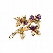 18k Yellow Gold Brooch, formed in a foliate motif and set with 22 small single cut diamonds and 4 full cut amethysts
