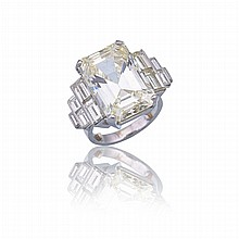 Platinum Ring, set with an emerald cut diamond (approx. 13.10ct.) flanked by 10 baguette cut diamonds (approx. 2.90ct.t.w.)